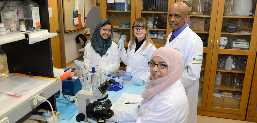 students and professor in the lab