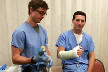 intern with arm casted; second intern lifting weight