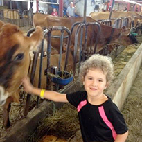 child petting cow