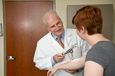 photo of a doctor looking at a patient's skin