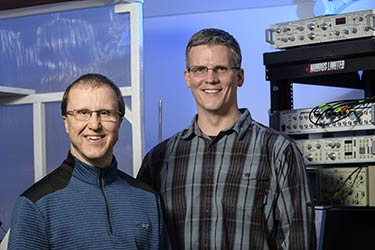 Two professors standing in front of a rack of equipment
