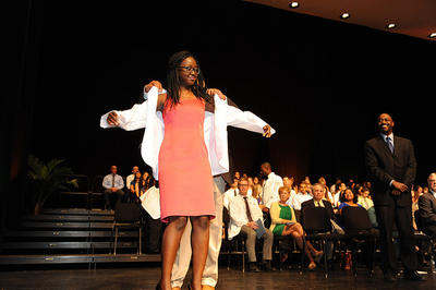 photo of a student receiving her white coat