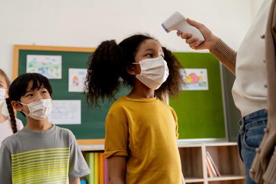 Child getting temperature checked.