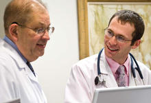 Photo of Larry Lawhorne, M.D., and Jess Levy, a third-year medical student, looking over an electronic health record (EHR) in the Wright State Physicians Family Medicine practice office.