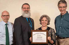 photo of faculty members with an award