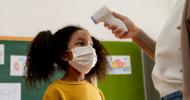 Young student in mask getting temperature taken